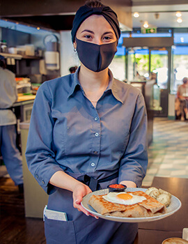An Anderson's Creperie staff member serving food