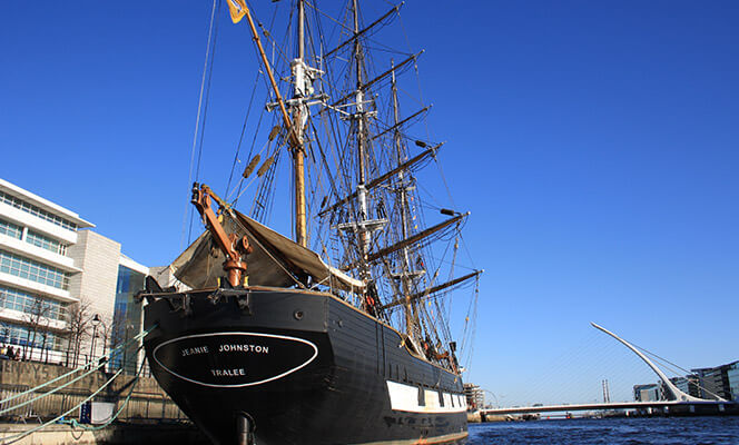 the old-fashioned jeanie johnston boat is anchored in the water in dublin neighbourhood grand canal dock
