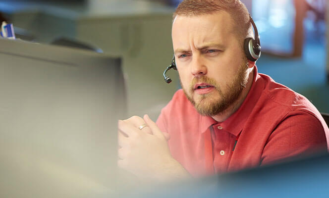 Man talking on phone headset in office for emergency services
