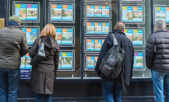 people looking at houses in estate agent window