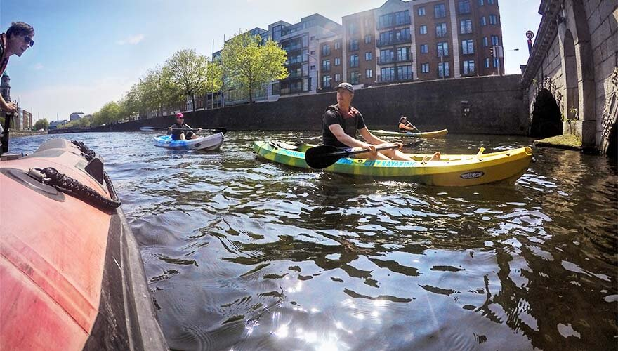 A tour group Kyaking along Dublin's River Liffey