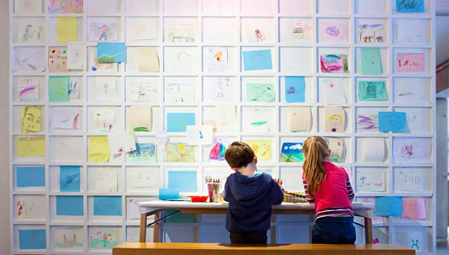 Children colouring in front of a display wall
