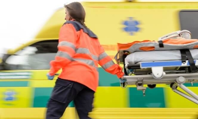 a paramedic pulls a stretcher from an ambulance