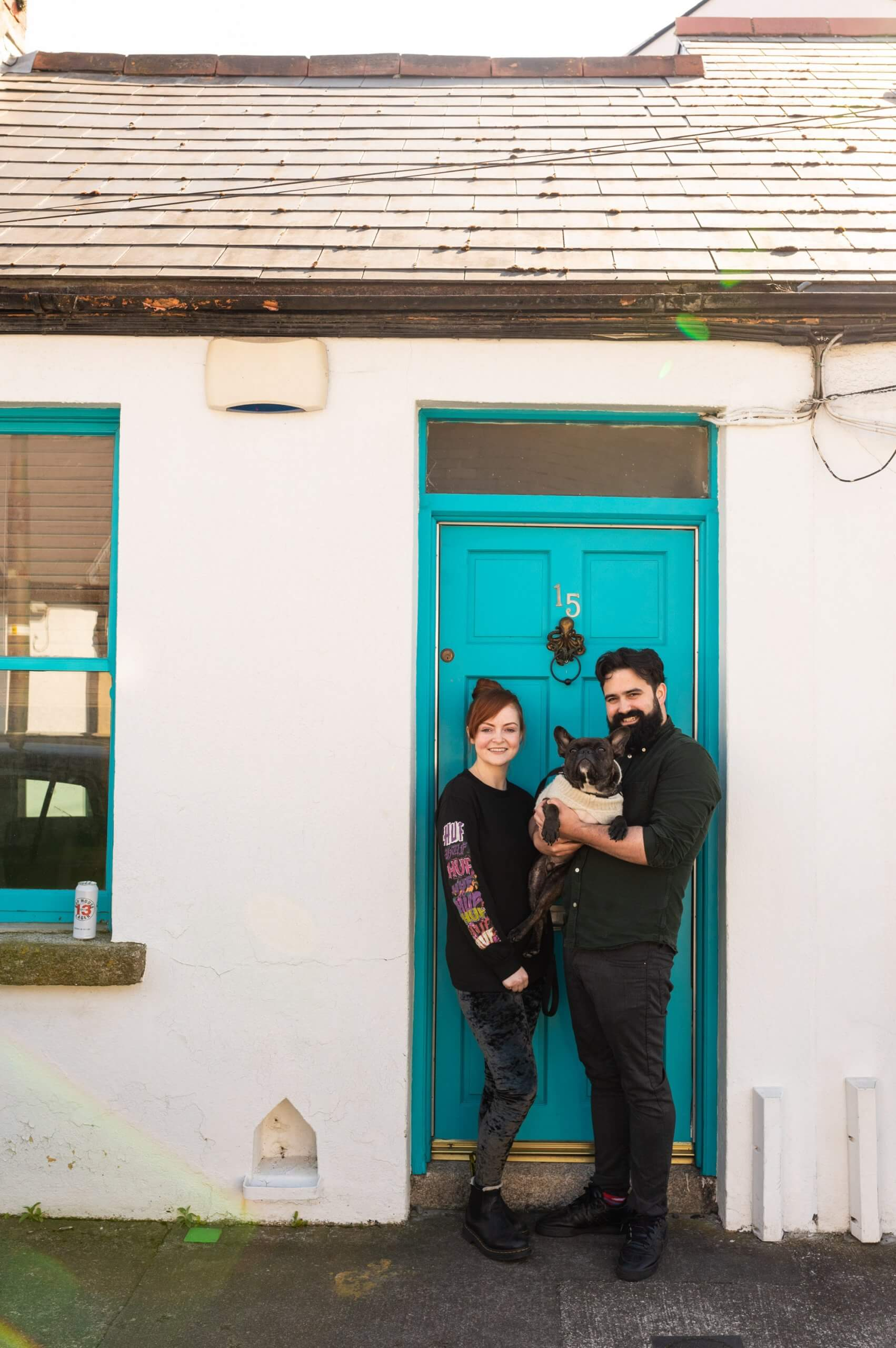 A couple and their dog pose at their front door