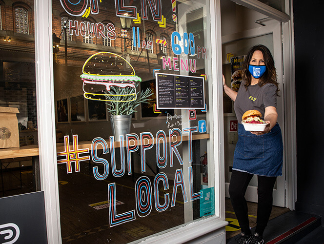 Food server in mask stands outside by a window display that says support local
