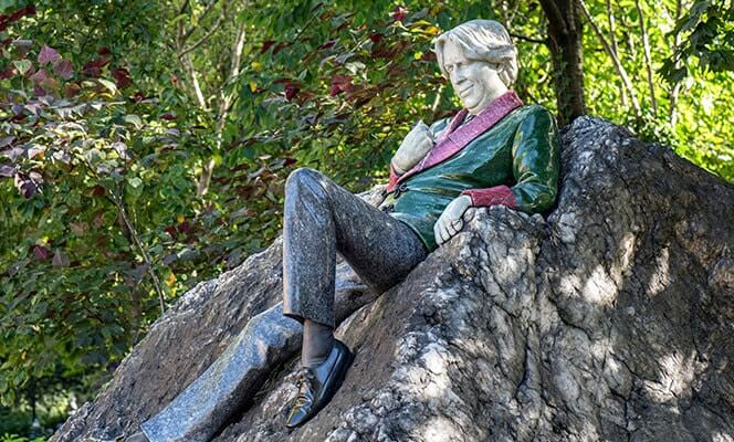sculpture of oscar wilde leaning back on a rock wearing a green and red jacket with black shoes